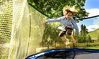 Boy jumping on a trampoline, South Tyrol, Italy, Europe