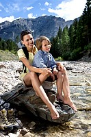 A woman and a boy sitting on a rock at the riverbank, South Tyrol, Italy, Europe