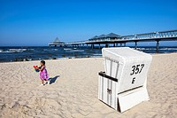 Little girl with beach toys, beach chair and pier, Heringsdorf, Usedom island, Baltic Sea, Mecklenburg_West Pomerania, Germany