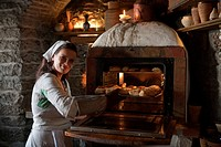 Woman in medieval costume bakes bread rolls and pies at Inn Krug Korts restaurant at Town Hall Square Raekoja Plats, Tallinn, Harjumaa, Estonia