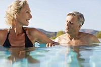 Retired couple soaking in pool
