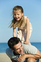 Little girl balancing on her father´s back