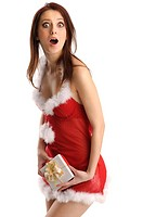 Surprised girl in a sexy santa claus outfit and a present