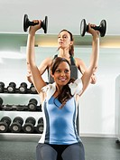 Trainer helping woman to use dumbbells