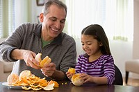 Grandfather and granddaughter peeling an orange