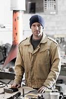 Caucasian metal worker standing in workshop