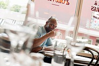 African American man drinking coffee in restaurant