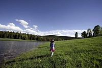 Young Girl in Field of Grass Near Mountain Lake, Rear View, Oak Creek, Colorado, USA