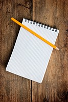 Notepad and pencil on the background of the wooden planks