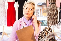 Hispanic business owner talking on cell phone in store