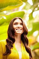 Smiling Caucasian woman standing in foliage