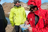 Hikers with a hiking map, Ammassalik Peninsula, East Greenland, Greenland