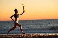 Silhouette of a woman running on the beach at sunset with a simulated Olympics relay torch