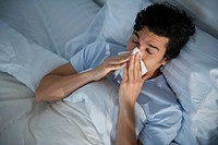 Man lying in bed and blowing nose