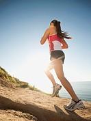 USA, California, San Diego, Woman jogging along sea coast