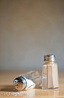 Flipped salt shaker spilling salt next to pepper shaker