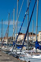 Boats are lined up in the small harbor of the Port of Marseillan in Southern France, just facing the Noilly Prat museum
