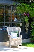 ARMCHAIR ON TERRACE IN FRONT OF GARDEN HOUSE