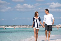 Couple walking on beach holding hands, portrait