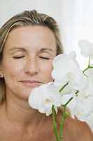 Woman smelling flowers, eyes closed