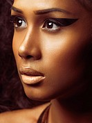 Exotic closeup beauty portrait of a young beautiful woman´s face with golden skin and artistic makeup