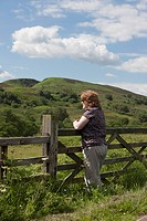 A Woman Stands Leaning Against A Wooden Fence And Looking At The Landscape, Northumberland England