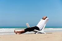 A Businessman Sits On A Beach Chair On The Beach Holding A Laptop Computer On His Lap, Tarifa Cadiz Andalusia Spain