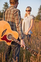 a couple standing in a field with a guitar, edmonton alberta canada