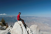 male hiker sitting on top of mountain peak over looking a desert valley with blue sky, palm springs california united states of america