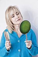 Middle-age blond woman holding a hairbrush and a hand mirror