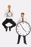 Businessmen holding clocks