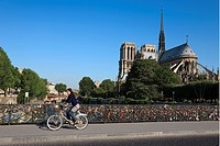 France, Paris, the banks of the Seine River listed as World Heritage by UNESCO, women cycling on the Archeveche bridge and Notre Dame Cathedral