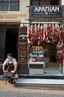 Greece, Athens, Fanis waits for the customers in front of his little butcher shop Arapian, in Evripidou street since 1922