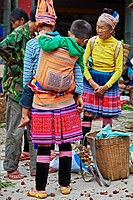 Tribal women in traditional dress at market in a small village, Yuanyang, Yuanyang county, Yunnan, China