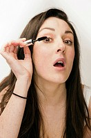A young woman with brown hair and eyes applying her makeup - putting on mascara