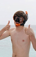 Young man wearing snorkel and diving goggles, thumbs up gesture, Maldives, Indian Ocean