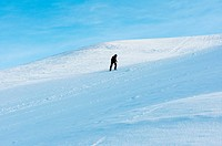 A lone man climbs a snow covered hill in Olympic park, Munich, Germany