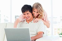 Man using laptop with woman watching him beside his head as they smile