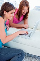 Laptop placed on a white sofa and used by two smiling women
