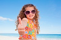 Girl standing on the beach giving thumb up