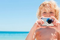 Boy using camera at the beach