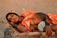 A hindu woman is sleeping while her baby is suckling. From a village in Thar desert, Rajasthan, India.