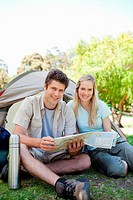 A smiling couple camp together with a map in hand