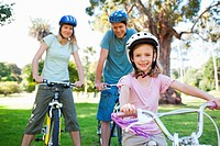 Parents and their daughter on bikes and wearing helmets