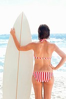 Woman holding a surfboard with one hand on her hip