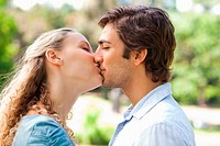 Side view of couple kissing in the park