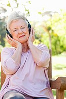 Woman listening to music while holding headphones to her ears