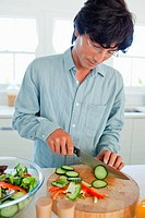 A man cuts cucumber into slices to add to a salad