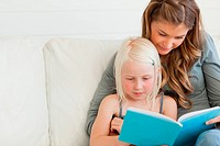 Close up of a girl and her mom reading a book together
