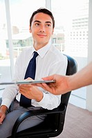 Handsome businessman showing a file